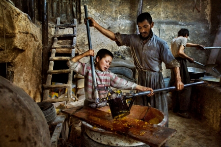 Hazaras, Kabul, Afghanistan, 2006, AFGHN-13034NF. A father helps his son make candy. MM7424_061007_11017 Confectionary factory, Kabul, Afghanistan, 2006. Pg 234. Untold: The Stories Behind the Photographs. retouched_Sonny Fabbri 11/14/2012