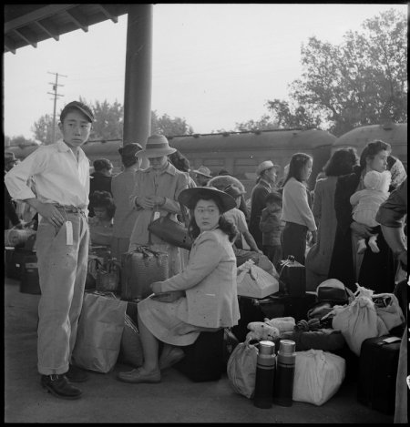Woodland, California. Families of Japanese ancestry with their baggage at railroad station awaiting . . .
