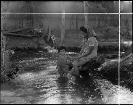 Manzanar Relocation Center, Manzanar, California. Evacuees enjoying the creek which flows along the . . .