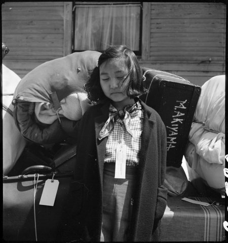 Oakland, California. Kimiko Kitagaki, young evacuee guarding the family baggage prior to departure . . .
